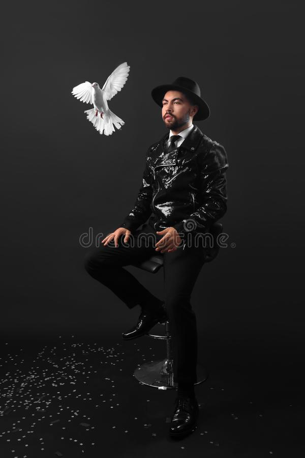 Male magician with white pigeon on dark background stock photography
