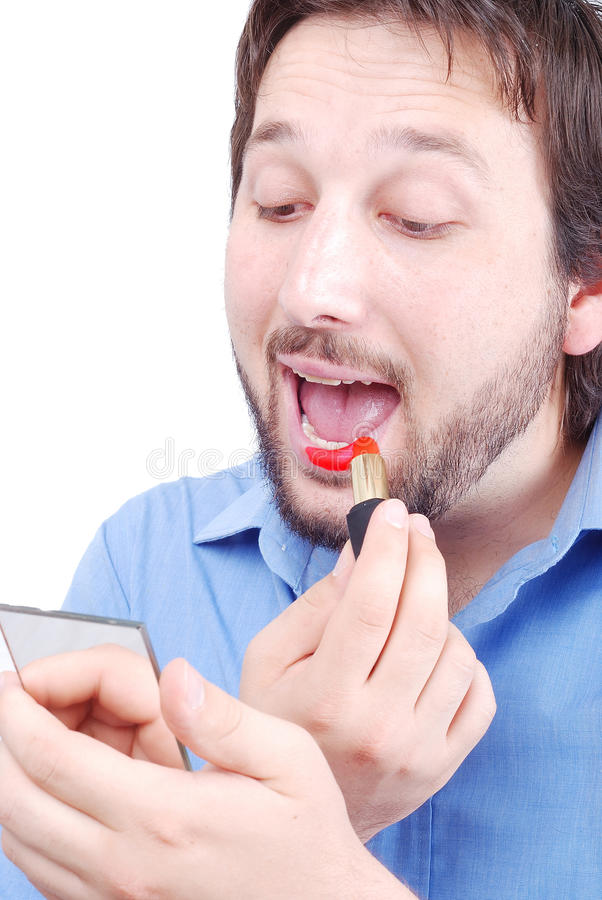 Male make up. Young man with a beard is putting make-up stock photo