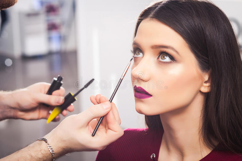 Male make-up artist doing brunette girl make-up in beauty salon, close-up. Cool male make-up artist doing brunette girl in a dress make-up in beauty salon, close stock photo