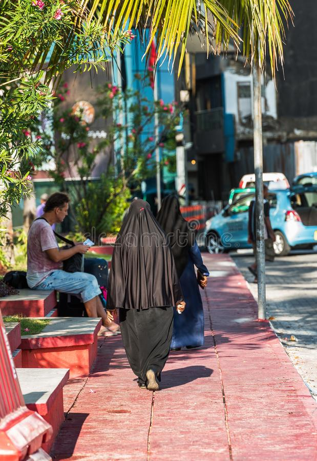 MALE, MALDIVES - NOVEMBER, 27, 2016: Woman in a black burqa on a city street. Copy space for text. Vertical. stock images
