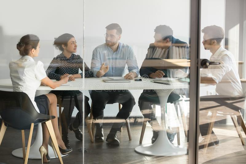 Male manager boss talking at group office meeting in boardroom. Male manager boss talking at group office meeting sit at conference table behind glass door stock photos