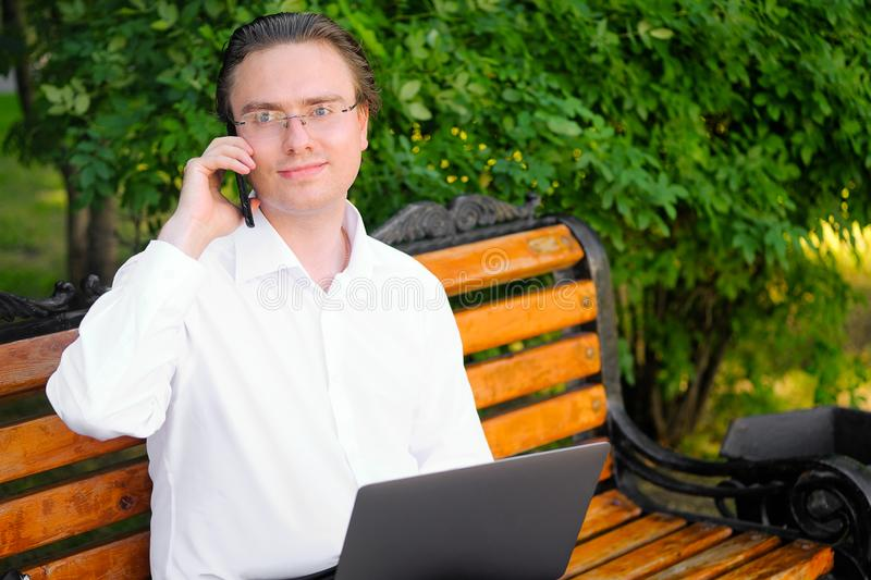 Male Manager, freelancer, businessman in glasses working on a laptop outdoors. Communicates, talking on a mobile phone, smiling royalty free stock photo