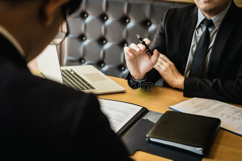 Male manager holds the pen and is explaining about the new employee work plan.  stock image