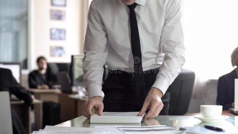 Male manager reading contract, preparing documents for meeting, planning agenda. Stock photo stock photos
