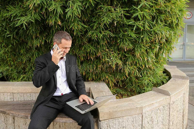 Manager talking by smartphone and working with laptop outside in stock image