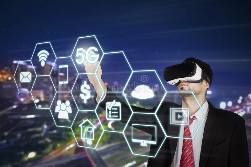 Male manager touching 5G network symbol. Fast data transfer concept. Male manager wearing virtual reality goggles while touching 5G network symbol on the virtual stock images
