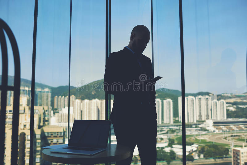 Male manager is using cellphone after work on net-book. Silhouette of a man is reading e-mail on mobile phone, while is standing against office window with view stock photo