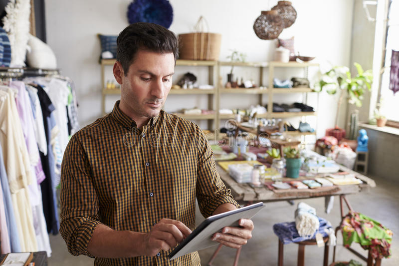 Male manager using tablet computer in clothes shop stock photos