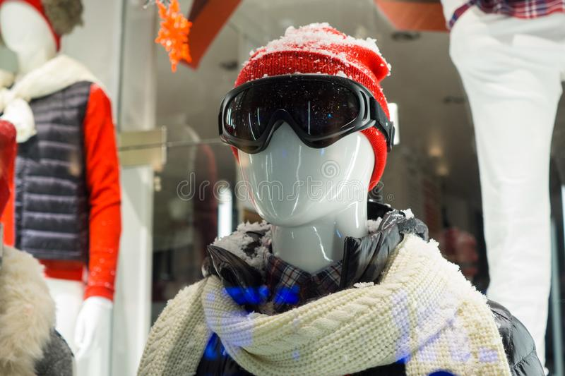 Male mannequin in store window during winter with ski gear, woolly hat, dark goggles, scarf, down jacket and fake snow on head stock photo
