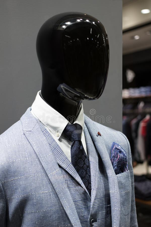 Male mannequin wearing a jacket and tie in a boutique window stock images
