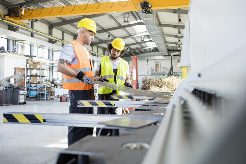 Male manual workers examining sheet metal at industry stock image