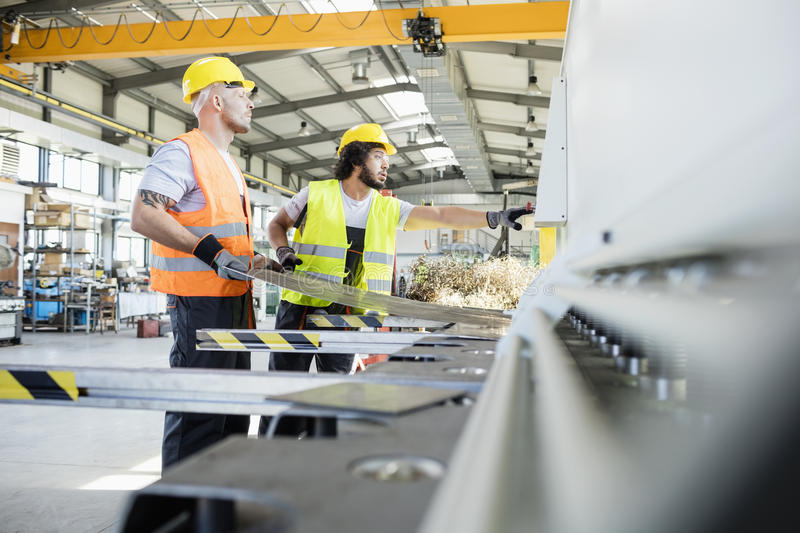 Male manual workers manufacturing sheet metal at industry stock photos