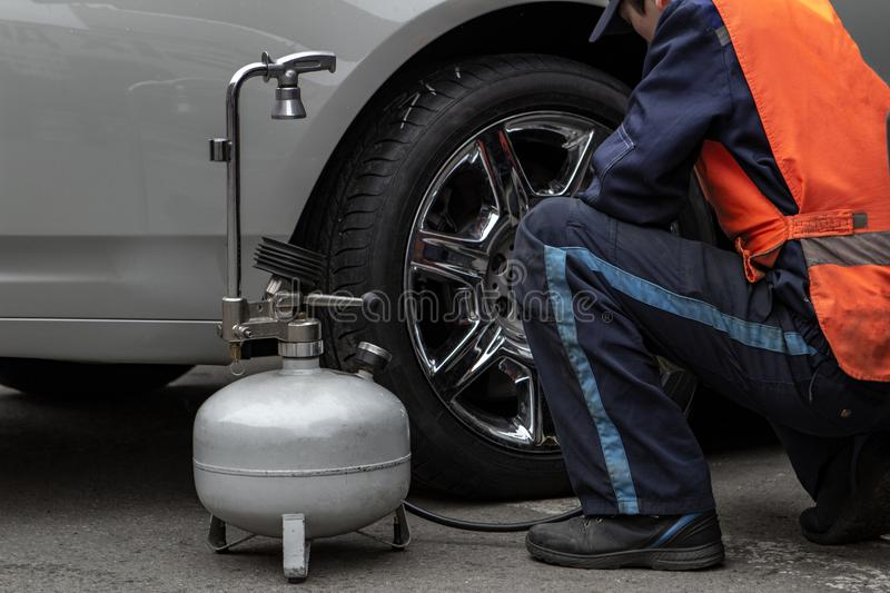 The male master changes the wheel and pumps the tires using a compressor stock photo