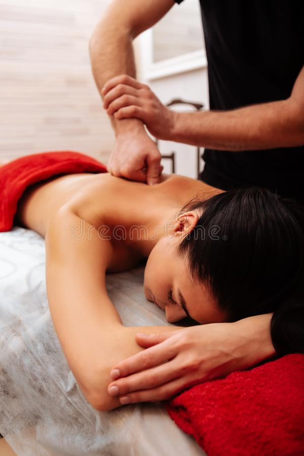 Male master of SPA center giving professional strong massage royalty free stock photo