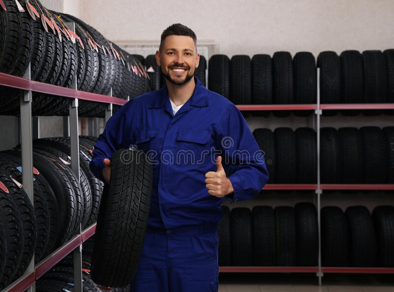 Male mechanic with car tire in store stock image