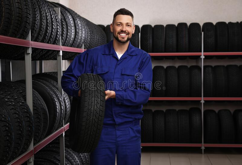 Male mechanic with car tire in store stock photo