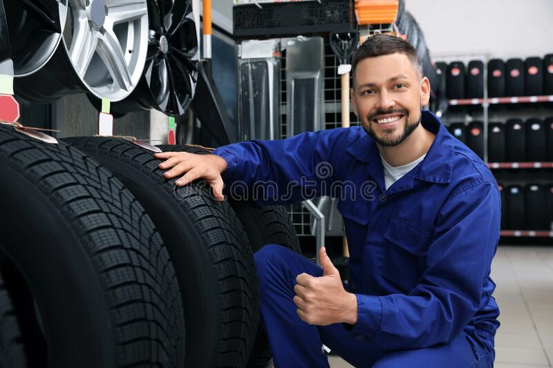 Male mechanic with car tires in store royalty free stock images