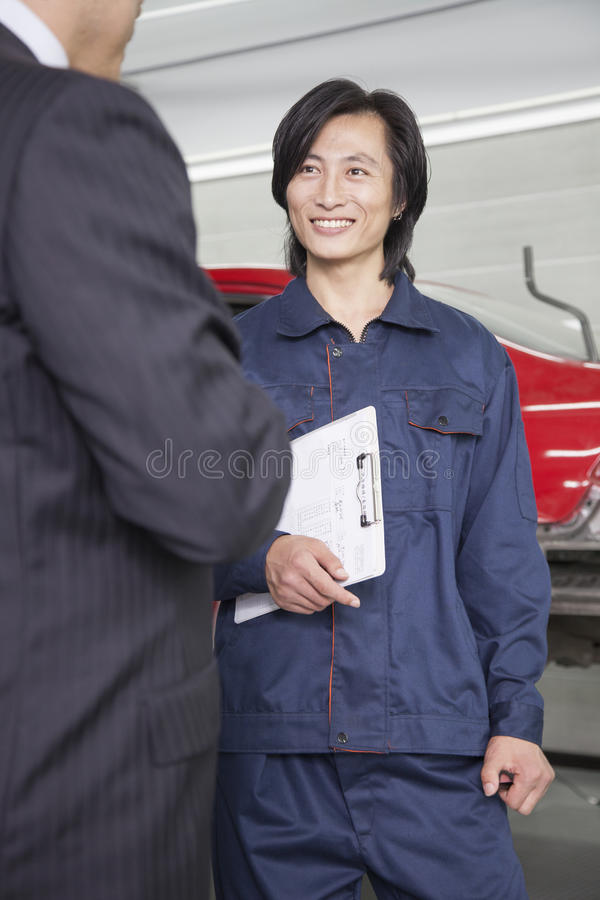 Male Mechanic with Customer in Auto Repair Shop stock images