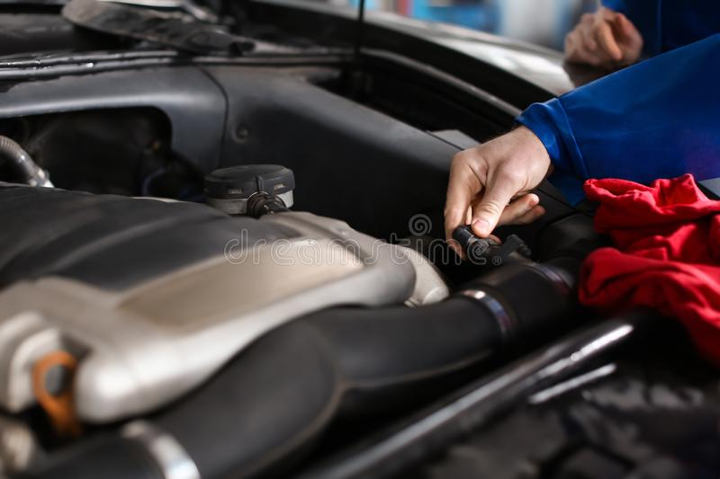 Male mechanic examining car in service center stock image