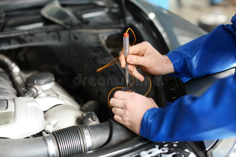 Male mechanic examining car in service center stock photography