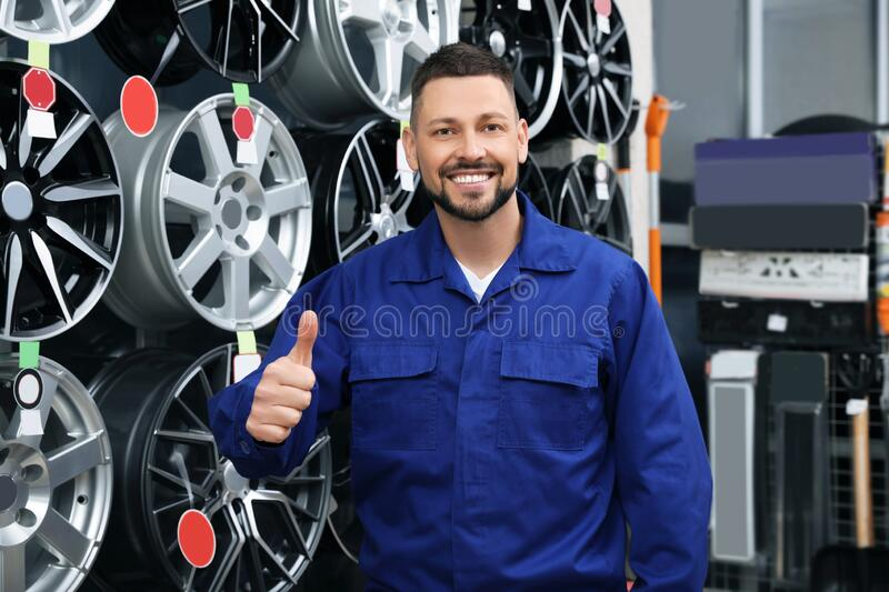 Male mechanic near alloy wheels in store royalty free stock images