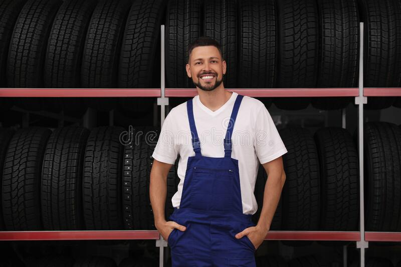 Male mechanic near rack with car tires in store stock images