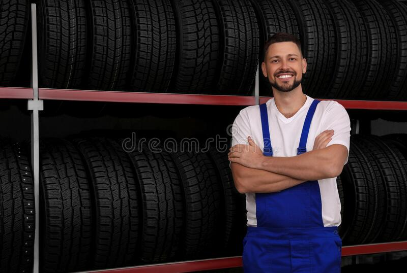 Male mechanic near rack with car tires in store royalty free stock photography