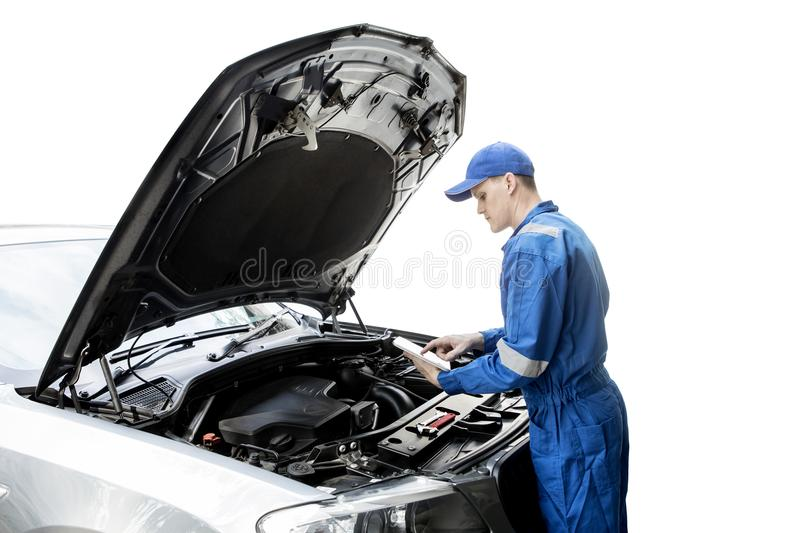 Male mechanic repairing a car with tablet. Image of young male mechanic using a digital tablet to repair a car engine, isolated on white background royalty free stock images