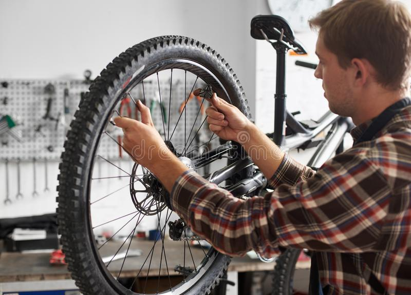 Male mechanic working in bicycle repair shop using tools royalty free stock photo