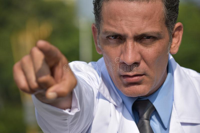 Male Medic Pointing Wearing Lab Coat. A handsome adult hispanic man stock photo
