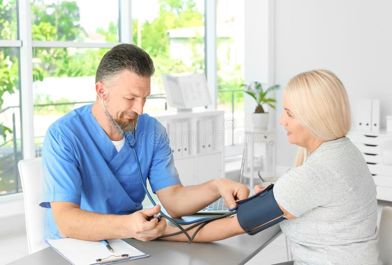 Male medical assistant measuring female patient. Blood pressure in clinic royalty free stock images