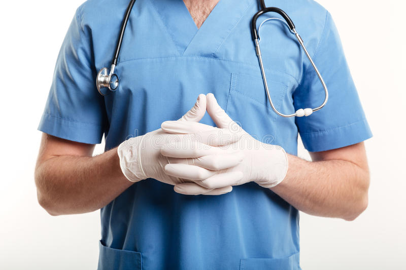 Male medical doctor or nurse wearing surgical gloves and stethoscope royalty free stock images