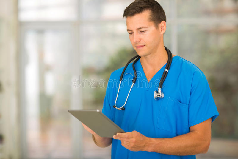 Male medical nurse. Successful male medical nurse using tablet pc in office royalty free stock photography