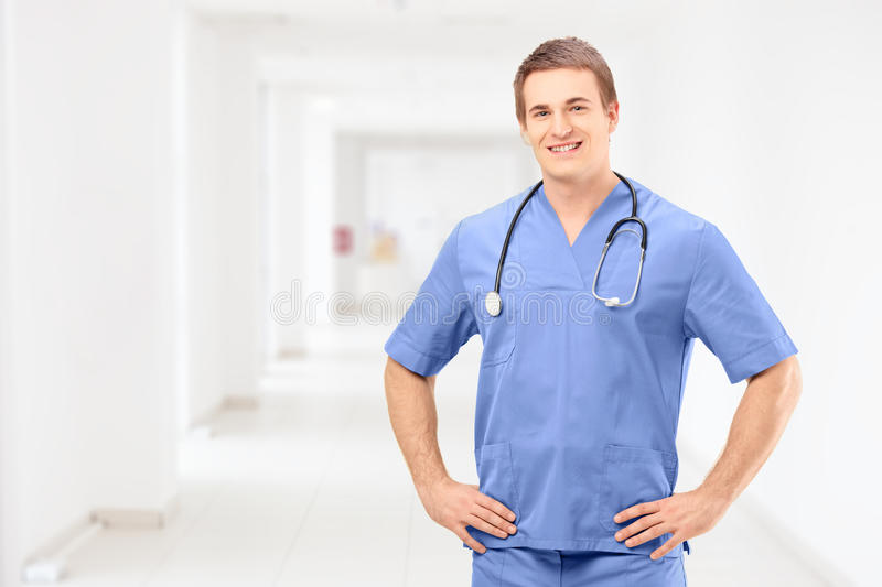 A male medical practitioner in a uniform posing in a clinic. A male medical practitioner in a uniform posing in a medical clinic stock photo