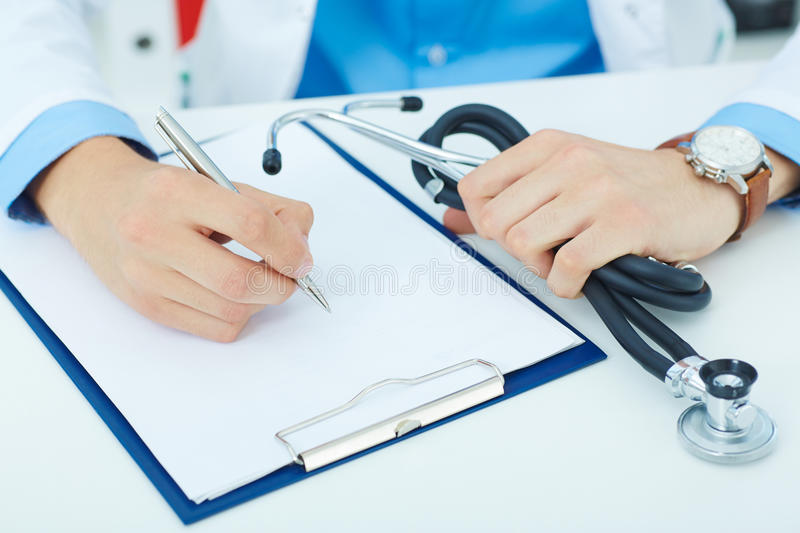 Male medicine doctor hand holding silver pen writing something on clipboard closeup. royalty free stock images