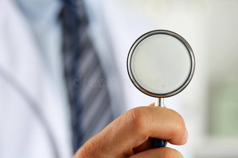 Male medicine doctor hand holding stethoscope head closeup royalty free stock photos
