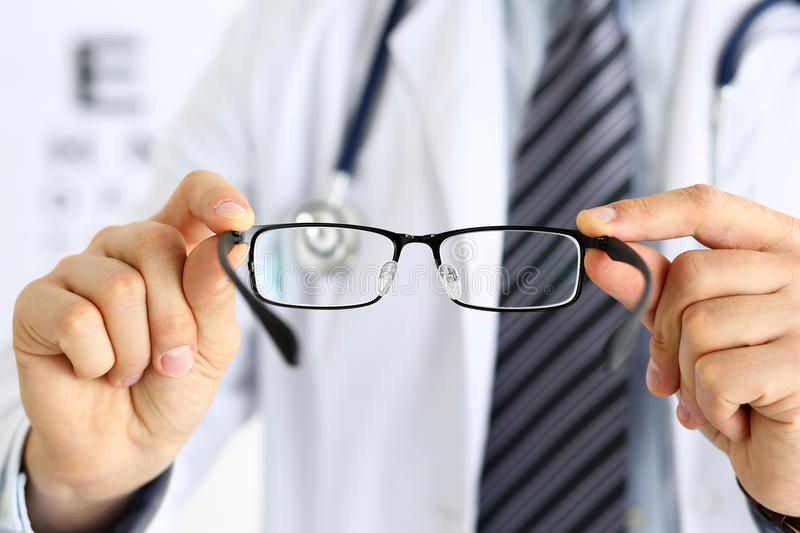 Male medicine doctor hands giving pair of black glasses. To patient. Eyesight test and correction, excellent vision, laser surgery alternative, driver health royalty free stock photography