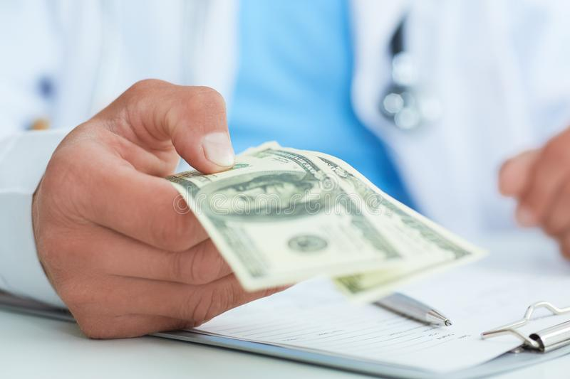 Male medicine doctor`s hand holding two hundred dollars banknotes closae-up. Medic personnel salary, prestige and high stock images