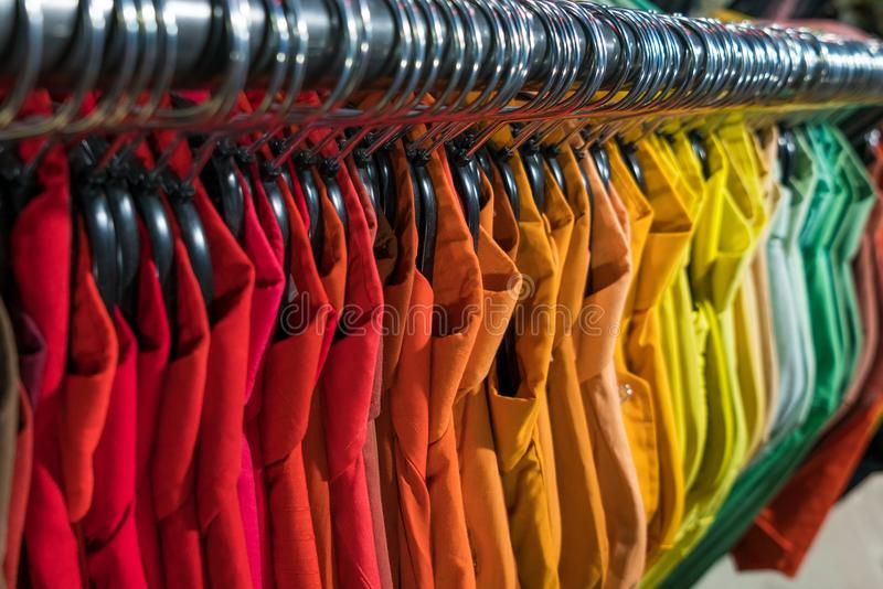 Male Mens Shirts on Hangers in Thrift Shop or Wardrobe Closet Ra. Male men's shirts sorted in color order on hangers on a thrift shop or wardrobe closet stock images
