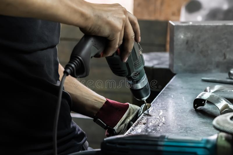 Male metal worker bore a piece of medieval armour suit. Man hand. S treating metal parts of hardware in a workshop with electric drill machine stock images