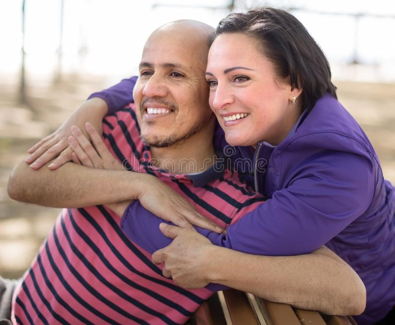 Male and middle-aged female posing on street bench. Happy male and nice female posing on street bench stock images