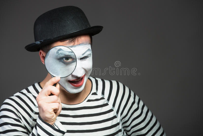 Male mime. Looking through the magnifying glass stock image