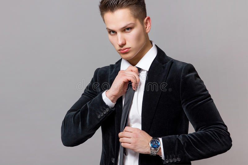 Male model in a black suit wears a watch royalty free stock photography