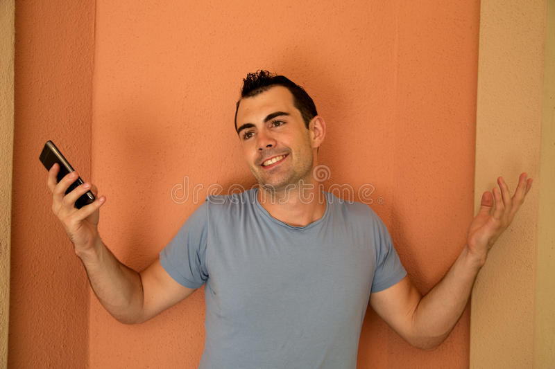 Male model with cell phone in hand showing a whatever attitude. Male model with a cell phone showing a whatever attitude stock photography