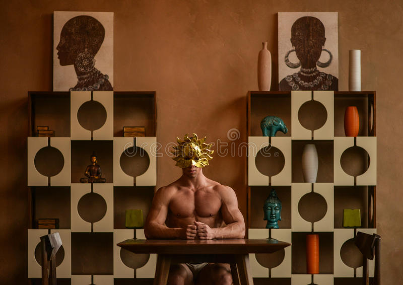 Male model in gold mask. Muscular teenage male model sitting at a desk (table) wearing a gold sun style mask surrounded by stylish shelving with vases and royalty free stock images