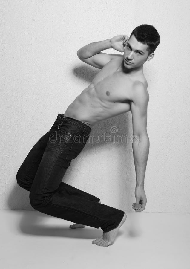 Male model in studio. Black and white studio portrait of a shirtless young man standing on his toes, bending backwards at the knees stock photography