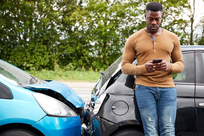 Male Motorist Involved In Car Accident Calling Insurance Company Or Recovery Service royalty free stock images