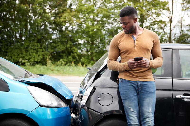 Male Motorist Involved In Car Accident Calling Insurance Company Or Recovery Service stock images