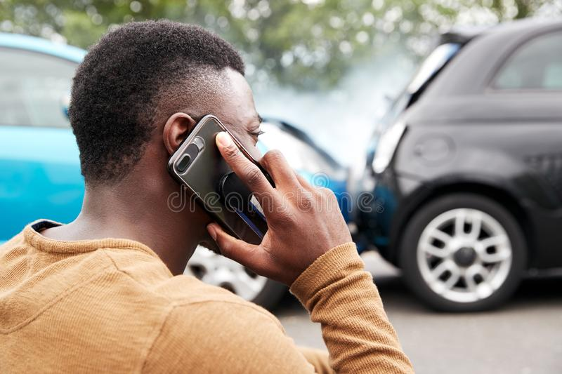 Male Motorist Involved In Car Accident Calling Insurance Company Or Recovery Service royalty free stock photo
