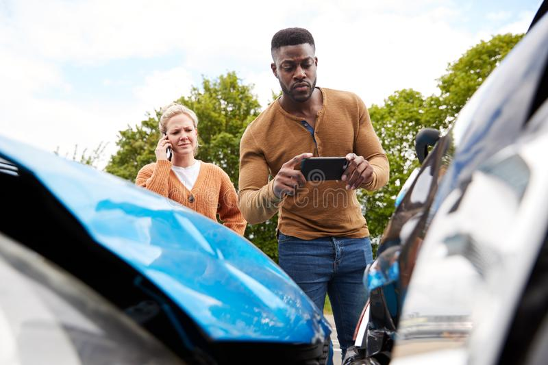 Male Motorist Involved In Car Accident Taking Picture Of Damage For Insurance Claim stock photos